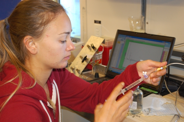 Lindsay Werra injects a sample into a gas chromatograph to be analyzed for methane.