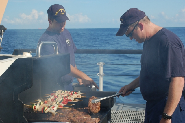 LCDR Jesse Stark assumes command of the grill from ENS Kurt Karpov