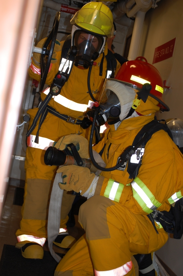 ENS Laura Gibson and Victor Coleman simulate fighting a fire during a drill onboard the NOAA Ship Pisces.