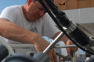 Electronics Technician Robert Carter sets up a water sampling instrument.