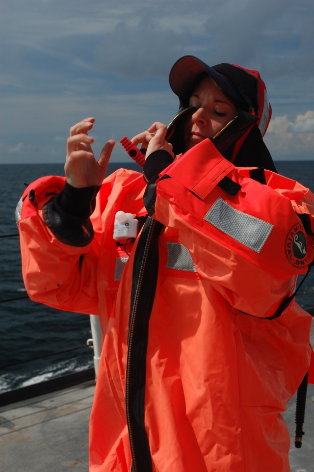 ENS Kelly Schill dons her survival suit during an abandon ship drill