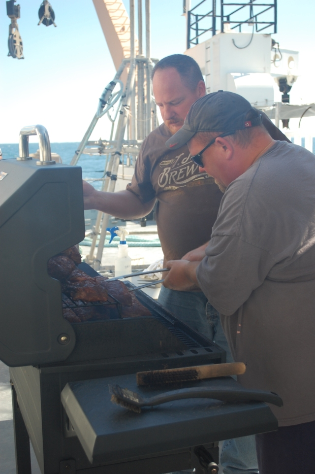 Erik Quiroz shows Dave Newman how ribs are done