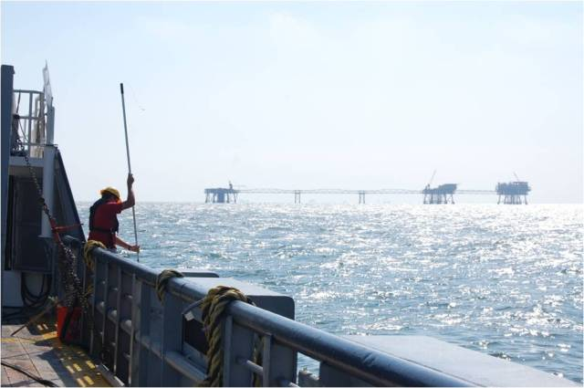 Ken Cerrito conducts a surface water sample with a backdrop of oil rigs